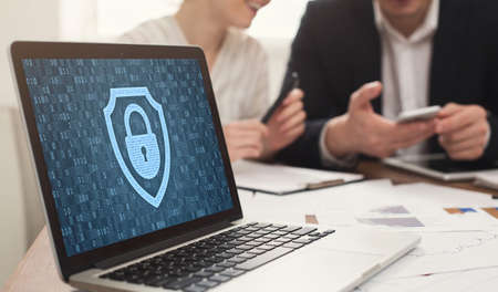 Data Protection And Corporate Cyber Security Concept. Laptop with closed padlock icon and binary code on the screen, business people in the background. Protect information from fraud and online crime