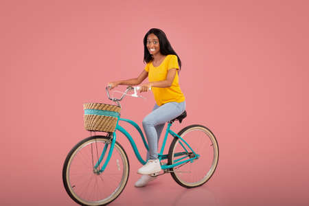 Full length portrait of beautiful African American woman riding vintage bicycle over pink studio background. Positive black lady on bike going cycling, enjoying her ride. Active lifestyle concept