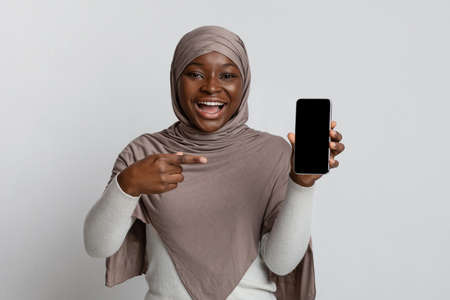 Cheerful Black Islamic Lady In Hijab Pointing At Smartphone With Black Blank Screen, Demonstrating Modern Gadget With Copy Space For Your Design, Standing Over Light Studio Background, Mockup Image Standard-Bild