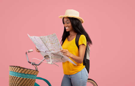 Lovely African American woman with bicycle looking at map over pink studio background. Pretty black lady in straw hat traveling by bike, plotting her tourist route