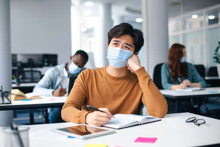 New Normal, Education And Studying Concept. Sad asian male student sitting at desk in classroom at university, wearing protective medical mask, writing in notebook and thinking, looking away
