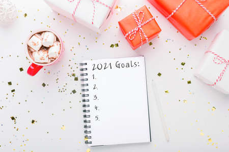 2021 Goals Concept. Notepad with new year resolutions, Christmas presents and cup of hot cocoa with marshmallows flat lay on white background with holiday decorations, creative background, top view