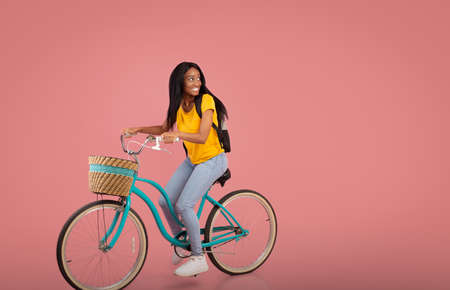 Pretty black lady riding bicycle and looking aside at empty space over pink studio background. Beautiful African American woman with bike going for ride, doing sports, having active hobby
