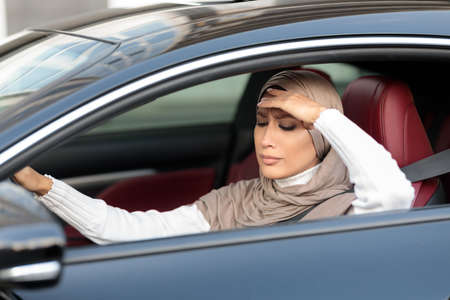 Upset and tired muslim woman in hijab driving car in urban city, got stuck in traffic jam. Sad arabic lady in headscarf touching head, feeling anxiety, headache or stress.