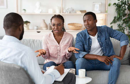 Unhappy Black Couple Having Meeting With Marital Counselor, Discussing Relationship Problems, Annoyed Young African Spouses Sitting On Couch At Therapyst Office In Need Of Professional Help