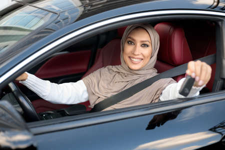 Car Buyer. Young Muslim Female Client In Hijab Smiling And Showing Automobile Keys Sitting In Her New Vehicle. Confident And Beautiful Middle East Woman Choosing Auto In Dealership Showroom Store Archivio Fotografico