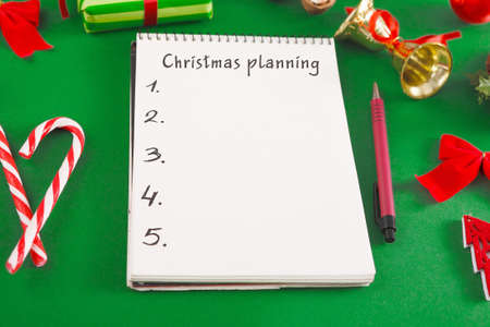 Cristmas Planning Creative Background With Notepad And Holiday Decorations Flat Lay On Green Table, Copy Space For Your Text Or Design, Top View