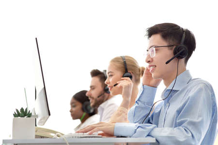 Diverse team of call centre operators working with computers at modern open space office. Group of helpdesk consultants managing customers requests through VoIP telephony