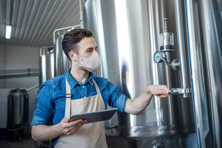 Small business, startup and modern craft brewery. Young man in apron and protective mask holds digital tablet with mobile app and operates equipment on large metal tank in factory, free space
