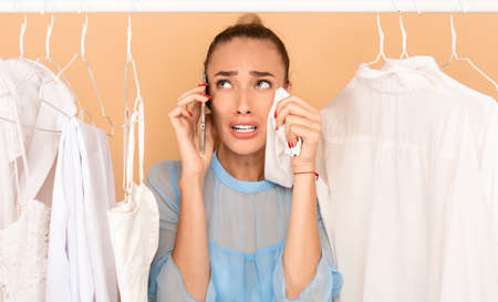 I Have Nothing To Wear. Portrait of upset stressed woman talking on mobile phone and crying, wiping tears with shirt, having panic, standing in rack of clothes between hangers