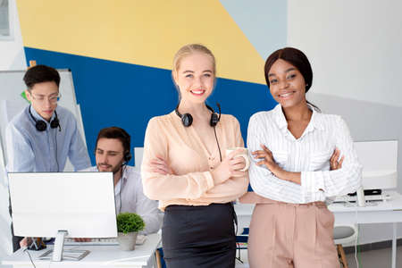 Portrait of female call centre operators smiling and looking at camera during their coffee break at modern office, free space. Positive customer support agents posing at workplace