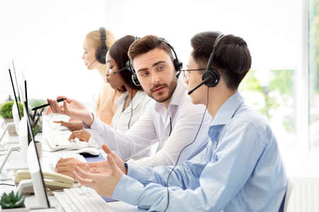 Male tech support operators communicating to solve clients request at call centre. Friendly young helpline consultants talking to each other at workplace. Hotline service concept