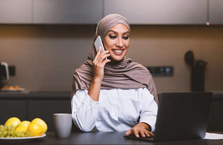 Muslim Lady Talking On Phone Using Laptop In Modern Kitchen At Home, Wearing Hijab. Smiling Arab Woman Calling Restaurant Ordering Food, Browsing Internet On Computer Indoors. Selective Focus