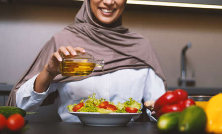Muslim Woman Cooking In Kitchen, Making Vegetable Salad With Oil Dressing At Home, Wearing Hijab Headscarf. Arabic Wife Preparing Healthy Dinner Working Indoor. Arab Cuisine, Recipes. Cropped Imagens