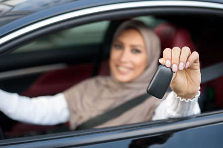 Test Drive New Car. Smiling Arabian Woman In Hijab Showing Automobile Keys Out Of Window, Sitting In Vehicle. Confident Middle East Lady Posing In Drivers Seat, Blurred Background, Selective Focus Stock Photo