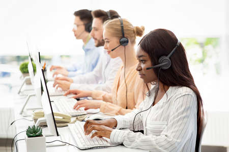Focused call centre operators with headphones working with computers at open space office, blank space. Multinational team of hotline managers providing telemarketing services to customers