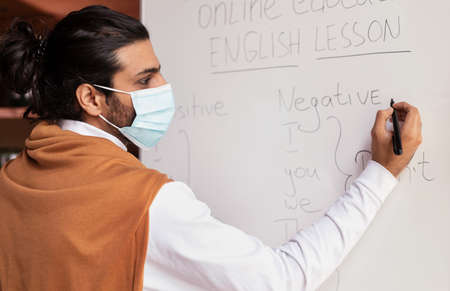 Correspondence Education Online. Indian Teacher In Mask Teaching English Grammar Writing Language Rules On Blackboard Standing Indoors. Distant E-Learning, Remote Class And Lesson. Selective Focus