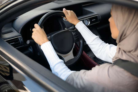 Test Drive. View over the shoulder of millennial Middle East woman in hijab driving her new luxury automobile. Muslim lady wearing scarf sitting in salon, holding steering wheel. Rent Concept