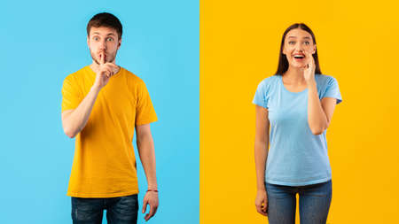 Young man gesturing hush sign, keep silence, smiling woman holding palm near mouth, making offer, screaming information at camera isolated over blue and yellow studio background wall 免版税图像