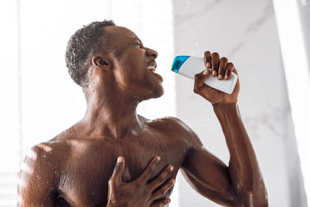 Black Man Singing In Shower Holding Shampoo Bottle Like Microphone Having Fun Bathing Standing In Modern Bathroom At Home. Hygiene And Male Bodycare Beauty Routine Concept.