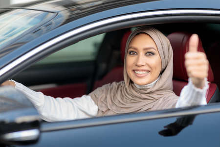 Happy Car Owner. Portrait Of Positive Middle East Lady In Hijab Showing Thumbs Up, Sitting In Drivers Seat, Happy About Purchase In Dealership Showroom. Excited Muslim Woman Making Approval Gesture Stock Photo