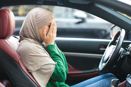 Stressed muslim female driver sitting in car, covering face with hands, having accident, failed driving test, annoyed of traffic jam, feeling headache. Depressed islamic woman crying in vehicle