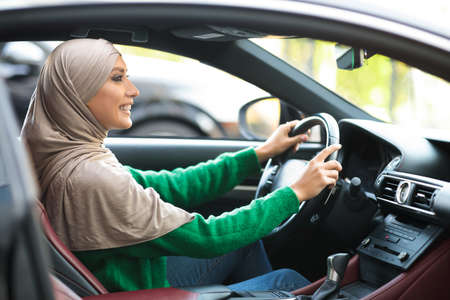 Test Drive Concept. Side View Portrait Of Cheerful Muslim Lady Driving Car In The City, Checking New Automobile, Buying Vehicle, Sitting On Drivers Seat, Holding Steering Wheel, Looking On Road Stock Photo