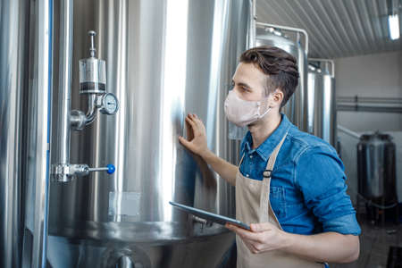 Work in modern brewery at covid-19 epidemic. Young worker in apron and protective mask hold digital tablet in hand and look at equipment in interior of modern production factory with big metal tanks