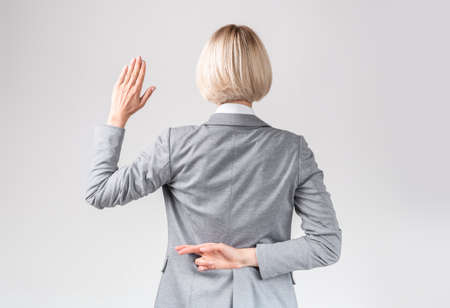 Female politician swearing oath with fingers crossed behind back on light grey studio background. Businesswoman making dishonest promise, lying or cheating, not saying truth
