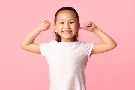 Fooling Around. Portrait of playful asian girl sticking fingers in her ears and goofing at studio, isolated on pastel pink studio background. Child grimacing, playing deaf, making faces, having fun