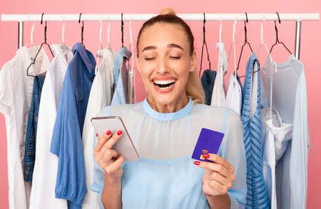 Easy Shopping Concept. Portrait of laughing stylish woman with closed eyes holding credit card and mobile phone, happy about purchase, ordering and buying clothes in online store via internet Foto de archivo