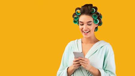Happy Housewife Using Smartphone Mobile Application Texting On Phone Standing Over Yellow Studio Background. Great App For Your Cellphone, Advertisement With Blank Space For Text. Panorama