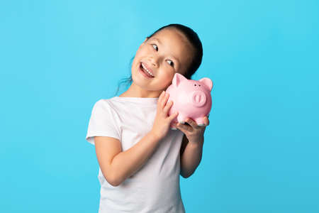 My Savings Concept. Portrait of positive asian girl shaking pink piggy bank and listening whats inside, isolated over blue studio wall, free space. Children And Economy, Personal Bank Standard-Bild