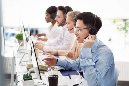 Telecommunications concept. Positive hotline consultants selling goods or services at call centre, copy space. Diverse team of tech support managers dealing with customers needs at modern office