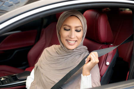 Safety First. Smiling Muslim Lady In Hijab Fastening Seatbelt Before Driving In City. Young Woman Sitting In Her Luxury Vehicle Car, Following Safe Ride Rules, Ready For Travel With Auto