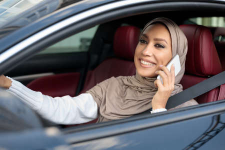 Modern Lifestyle. Portrait of smiling muslim woman in hijab driving new luxury car, talking on mobile phone. Cheerful arabian lady in headscarf sitting in salon on driver seat, holding steering wheel Stock Photo
