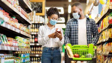African Family Couple In Shop Buying Groceries Wearing Face Mask Choosing Food Goods Walking With Shopping Cart In Supermarket Store. Customers Buy Essentials During Pandemic. Panorama, Free Space Stock Photo