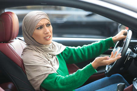 Angry muslim woman arguing with someone while driving car, sitting on front seat and emotionally gesturing. Annoyed arab lady stuck in traffic jam, having road accident, complaining about bad drivers