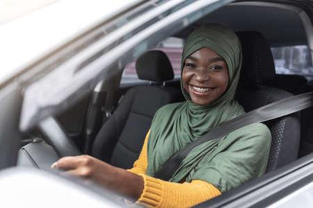 Portrait of joyful african muslim woman in car, enjoying road trip, smiling black islamic lady in hijab driving her new vehicle, holsing steering wheel and smiling at camera, closeup shot Stockfoto