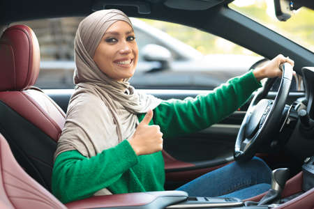 Driving School. Portrait Of Happy Middle East Woman In Headscarf Showing Thumbs Up Sitting Inside Luxury Car. Smiling Muslim Female Client Making Appoval Gesture, Got Her Driving License