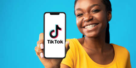 KHARKIV, UKRAINE - JULY 31, 2020: Black girl with braces showing cell phone with Tik Tok application on white screen