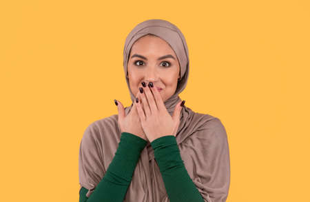 Muslim Lady In Hijab Covering Mouth With Hands Posing Smiling To Camera Standing Over Yellow Studio Background. Rumors Spreading, Oops, Slip Of A Tongue And I Didnt Say It Concept