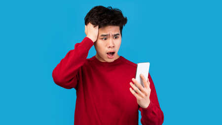 Oh No. Portrait of emotional shocked asian guy holding and using smartphone, seeing surprising news, photos or message. Surprised man grabbing head isolated over blue studio background wall