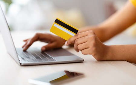 Modern Shopper. Side view closeup of unrecognizable black lady showing credit card and using laptop computer, making online financial transaction, paying bill, ordering presents, phone on the table