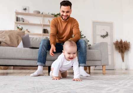 Happy Daddy Looking At Baby Crawling On Floor In Living Room At Home. Father Having Paternity Leave Caring For Little Toddler. Child Care, Cute Fatherhood Moments. Selective Focus