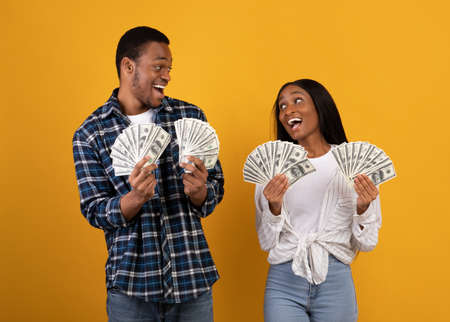 A lot of money and win. Millennial african american male and female hold many dollars in hands and expressing success at covid-19 quarantine, isolation on yellow background, studio shot, copy space