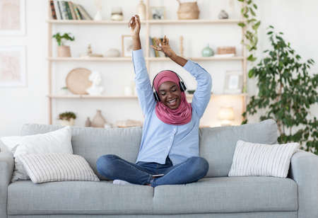 Joyful black muslim woman in hijab listening favourite music in wireless headphones at home, having fun and dancing with eyes closed while sitting with smartphone on couch in living room, copy space