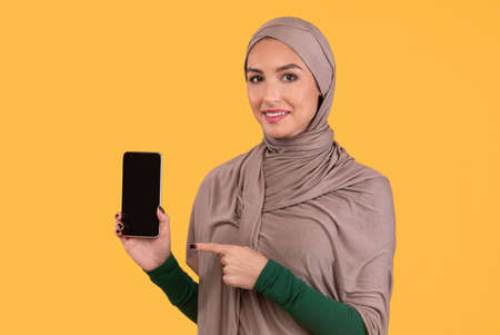 Great Mobile App. Muslim Lady Pointing At Smartphone Empty Screen Recommending New Phone Application Posing On Yellow Studio Background. Islamic Woman Approving Cellphone Apps. Mockup