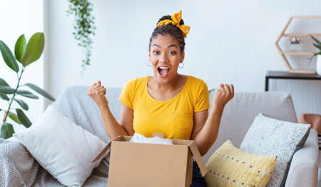 Yes. Emotional black female buyer customer received long-awaited package, screaming with joy, opening cardboard box at home, satisfied with great purchase. Reliable postal courier service concept