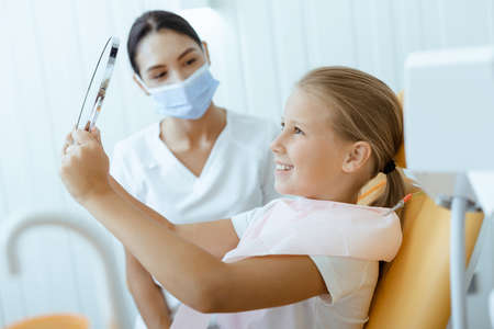 Great dentist work and perfect kids teeth. Happy little girl in medical chair looks in mirror, young female doctor in protective mask and uniform looks at baby in modern clinic at daylight, free space Фото со стока